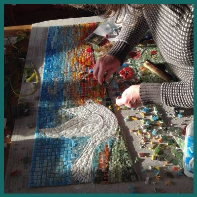 Siddy making a mosaic of a dove in a Devon landscape
