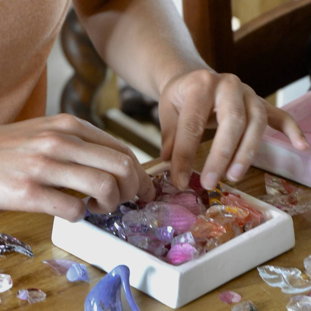 """Student arranging """"waste"""" glass in a tile mould for fusing"""